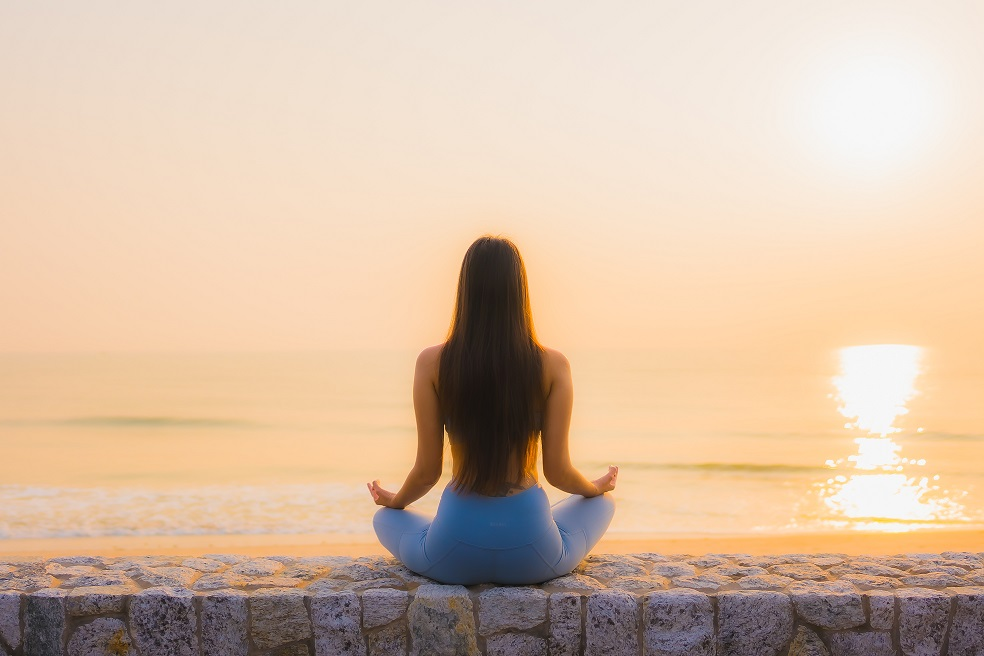 Fotografía de mujer meditando playa